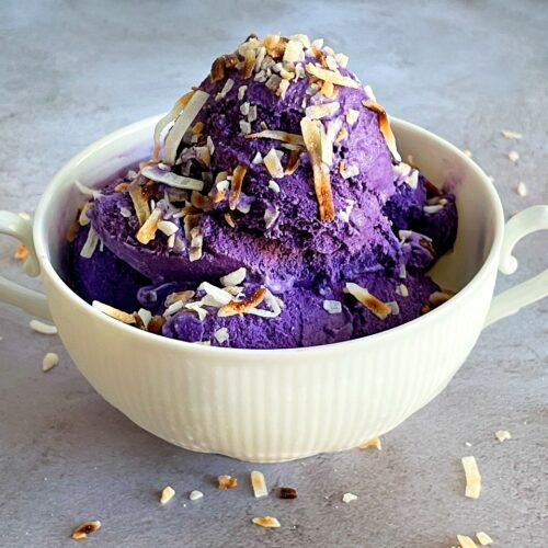 ube ice cream in a bowl with toasted coconut on top