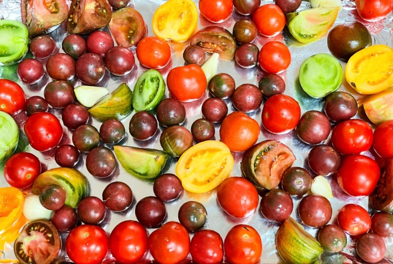 fresh heirloom tomatoes and garlic on a baking sheet