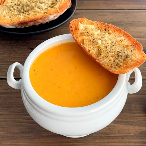tomato soup in a bowl with garlic bread