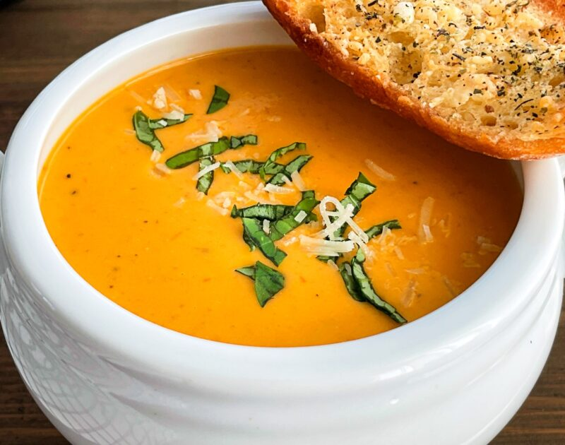 tomato soup with fresh basil and parmesan cheese on top